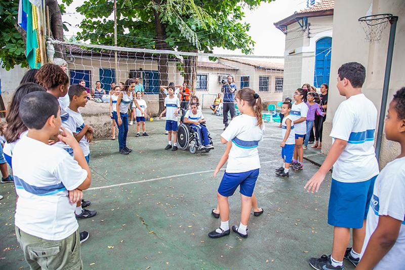 Crianças divididas em dois times em quadra dividida por rede jogam reaction ball.