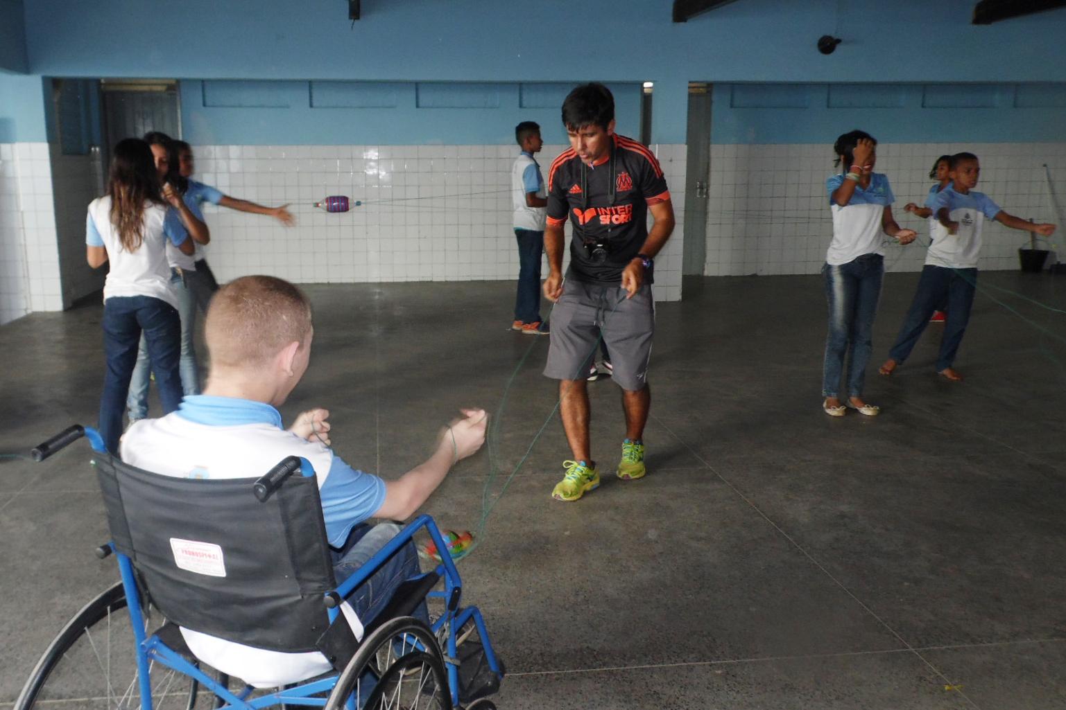 Alunos e o professor de educação física brincam com balangandã no pátio da escola.