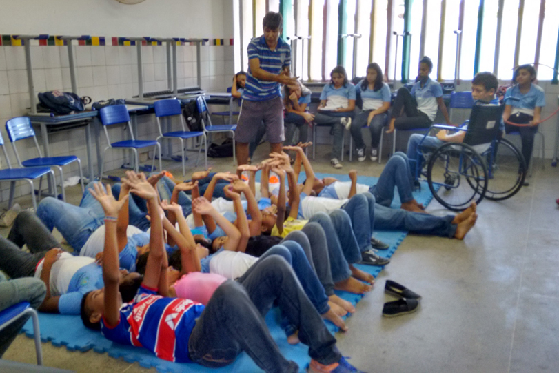 Um grupo de cerca de 20 crianças deitadas sobre colchonetes em uma sala de aula esticam os braços para cima. O professor de educação física supervisiona a atividade ao lado.