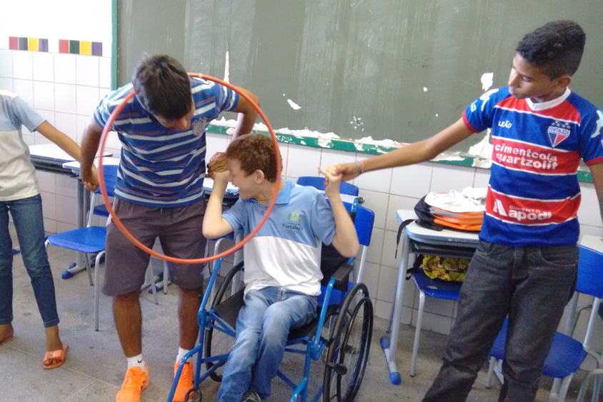 Um grupo de quatro pessoas está de mãos dadas. Uma delas, o professor, passa um bambolê com a cabeça para o aluno em uma cadeira de rodas ao seu lado.