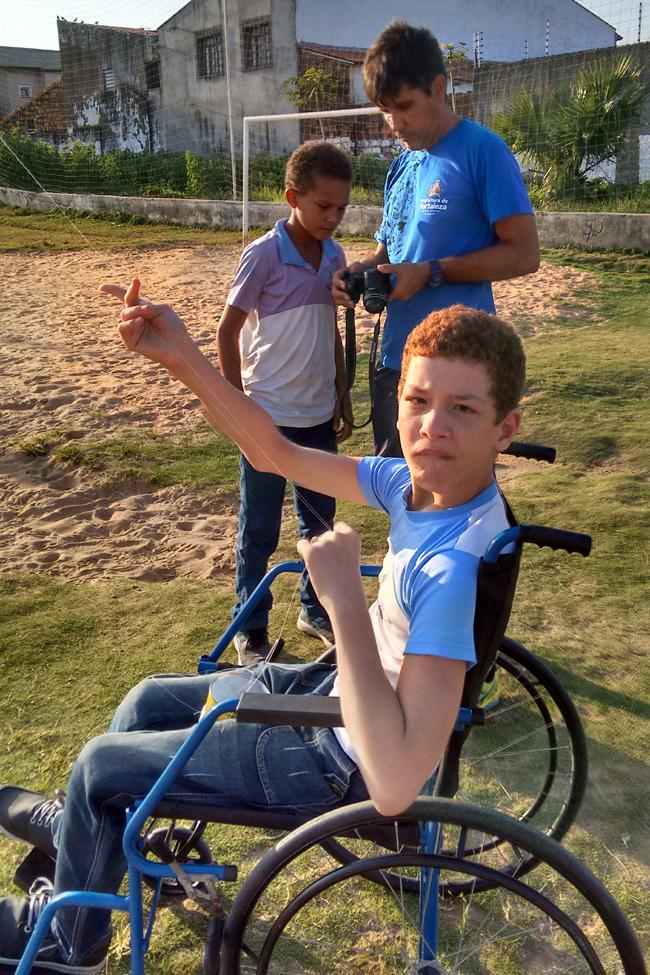 Um garoto de cerca de 10 anos em uma cadeira de rodas está em um campinho de terra e grama. Seu professor e um colega de classe aparecem atrás.