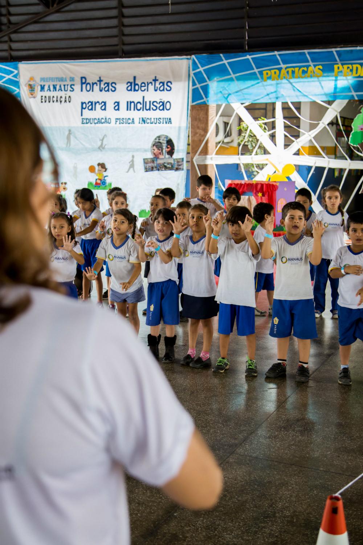 Diversas crianças fazem gestos com a mão diante de professora, que as guia.