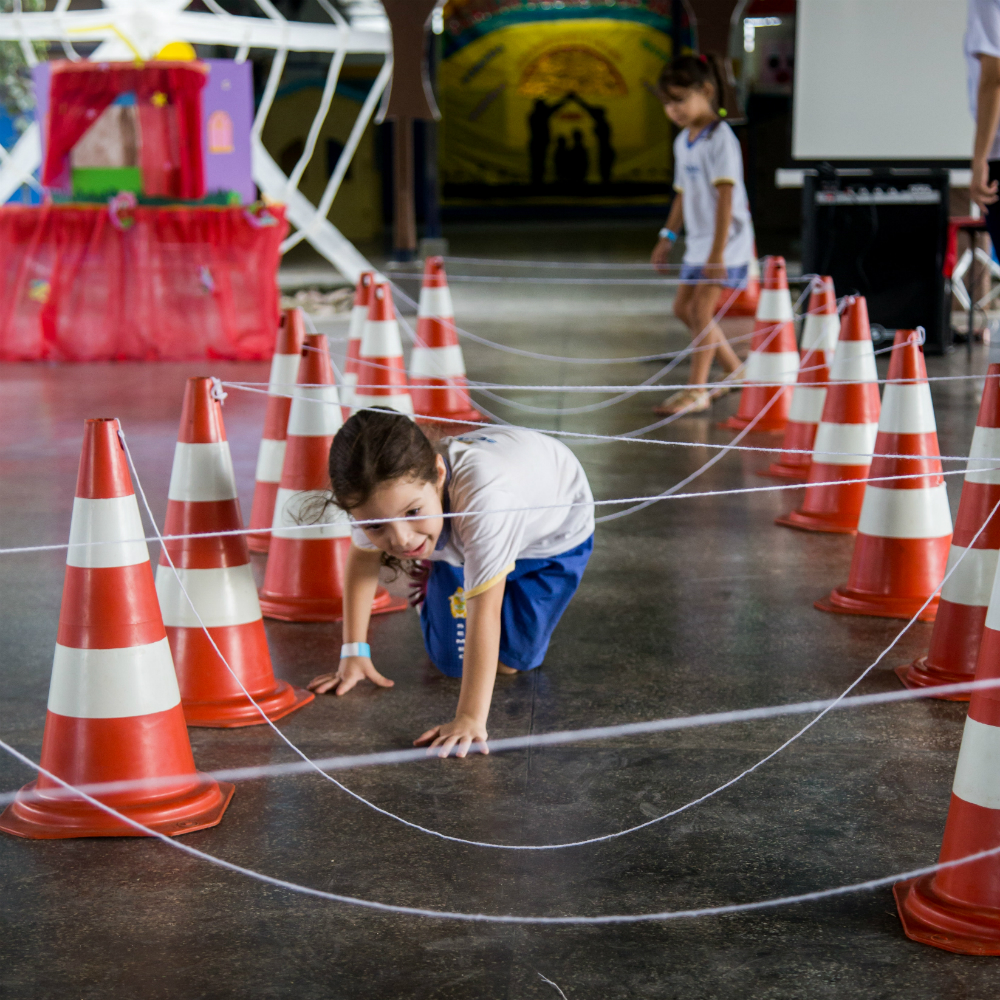 Uma menina de cerca de 5 anos de idade passa por baixo de um túnel formado por trama de fios que estão amarados no topo de cones.