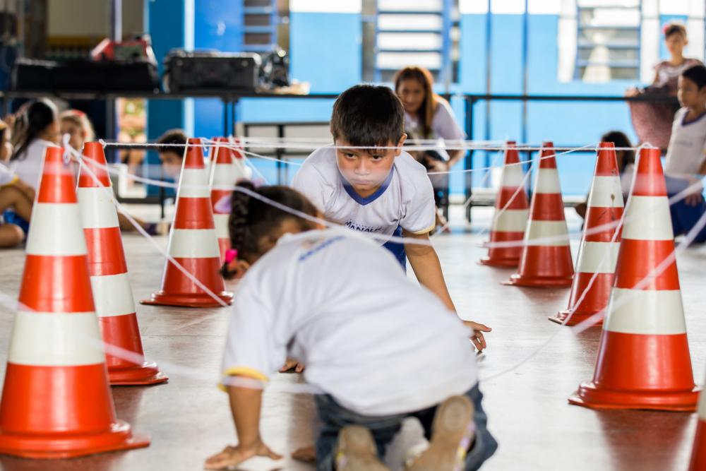 Duas crianças agachadas atravessam um túnel feito de fios e cones.