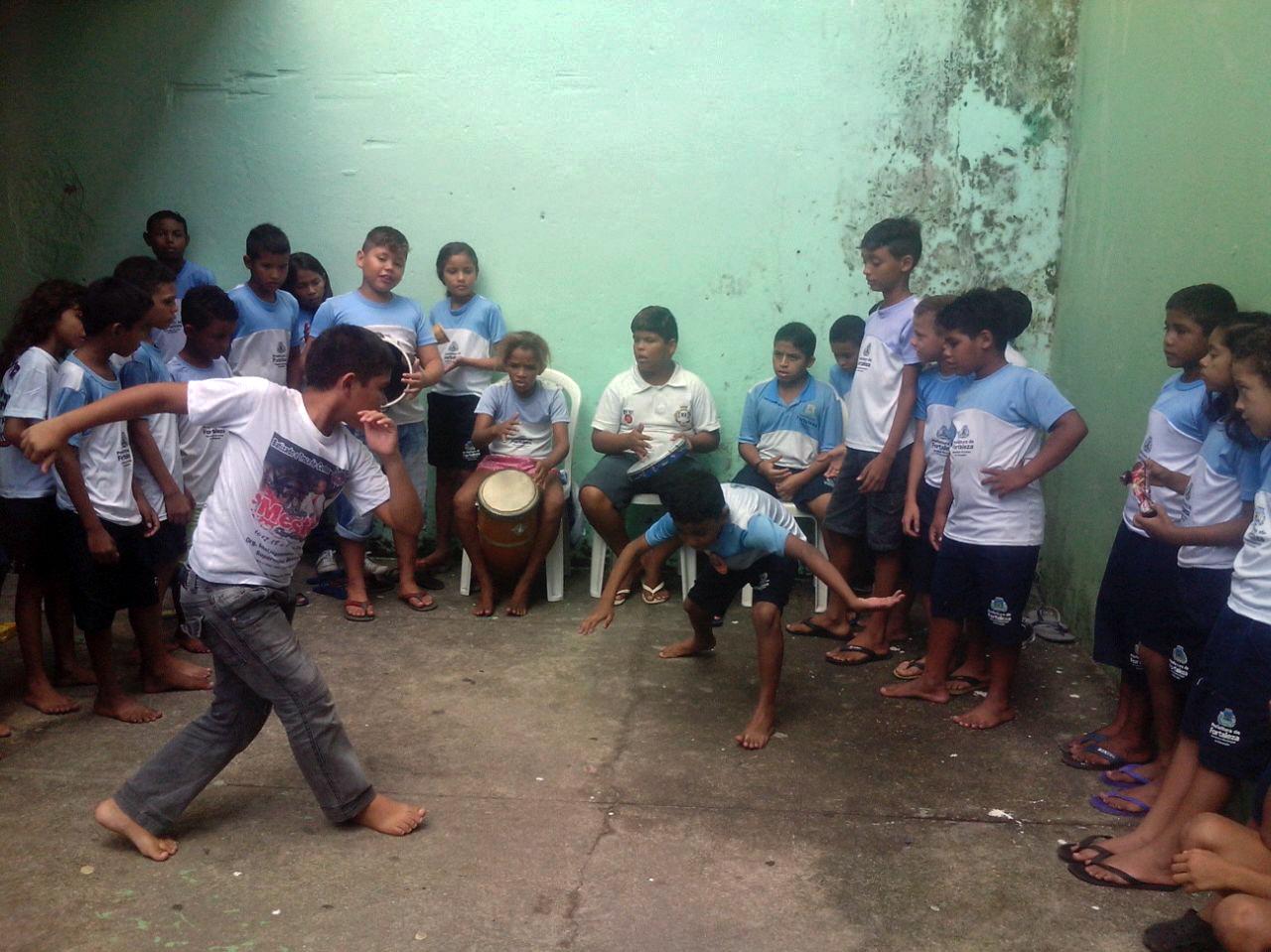 Um grupo de aproximadamente 20 crianças realiza uma roda de capoeira no pátio da escola.