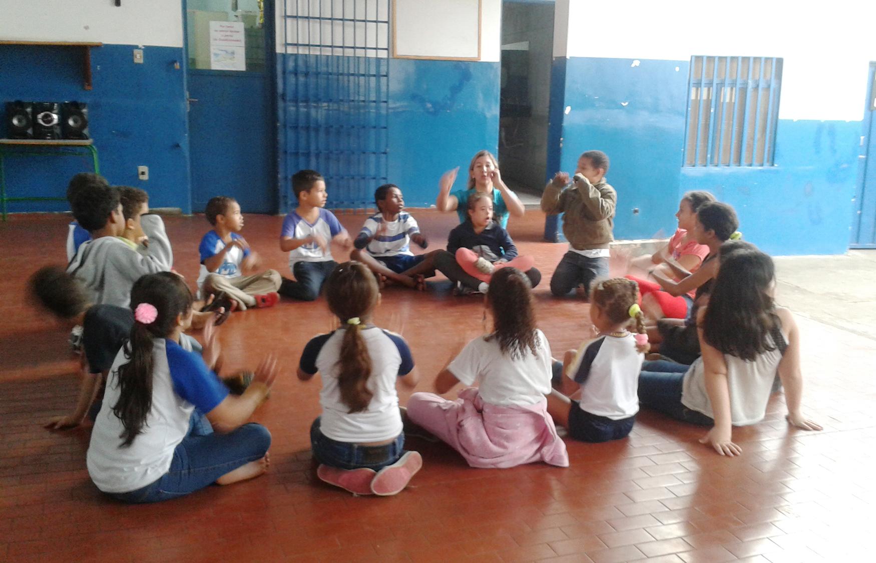 Crianças em uma quadra sentadas em círculo brincam de ciranda.