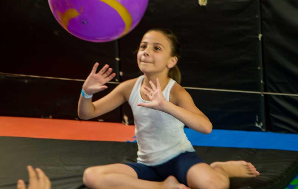 Garota sentada em colchonete arremessa grande bola para cima.