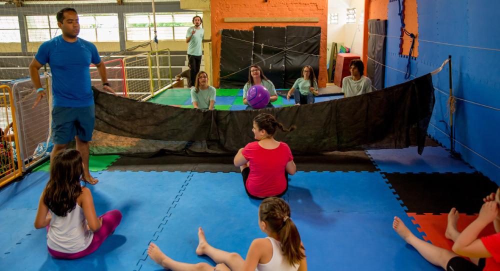 De pé, educador dá instruções para time de jovens em chão acolchoado durante partida de vôlei sentado.
