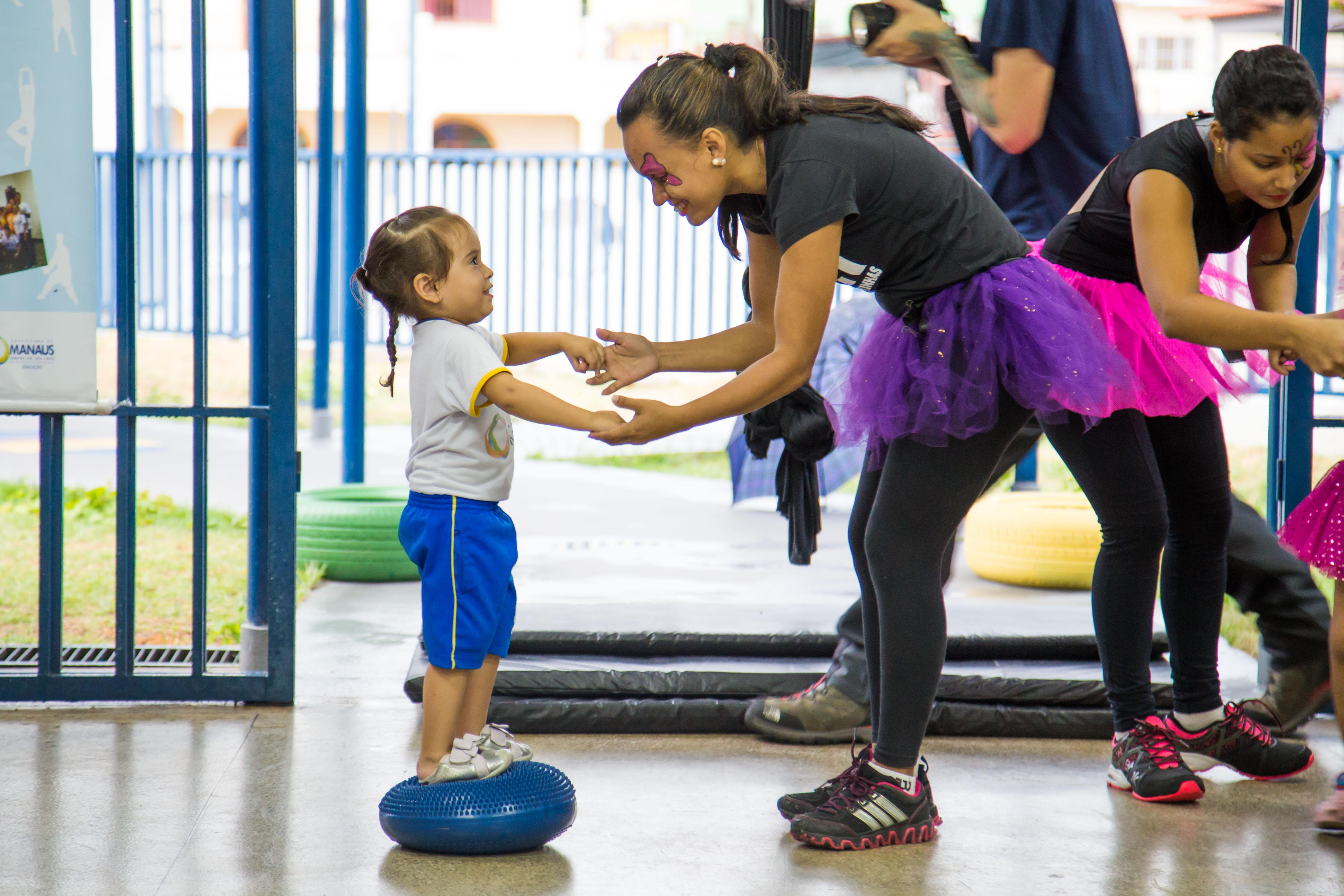 Uma garota pequena está em pé sobre um disco inflável de borracha enquanto segura as mãos de uma das professoras.