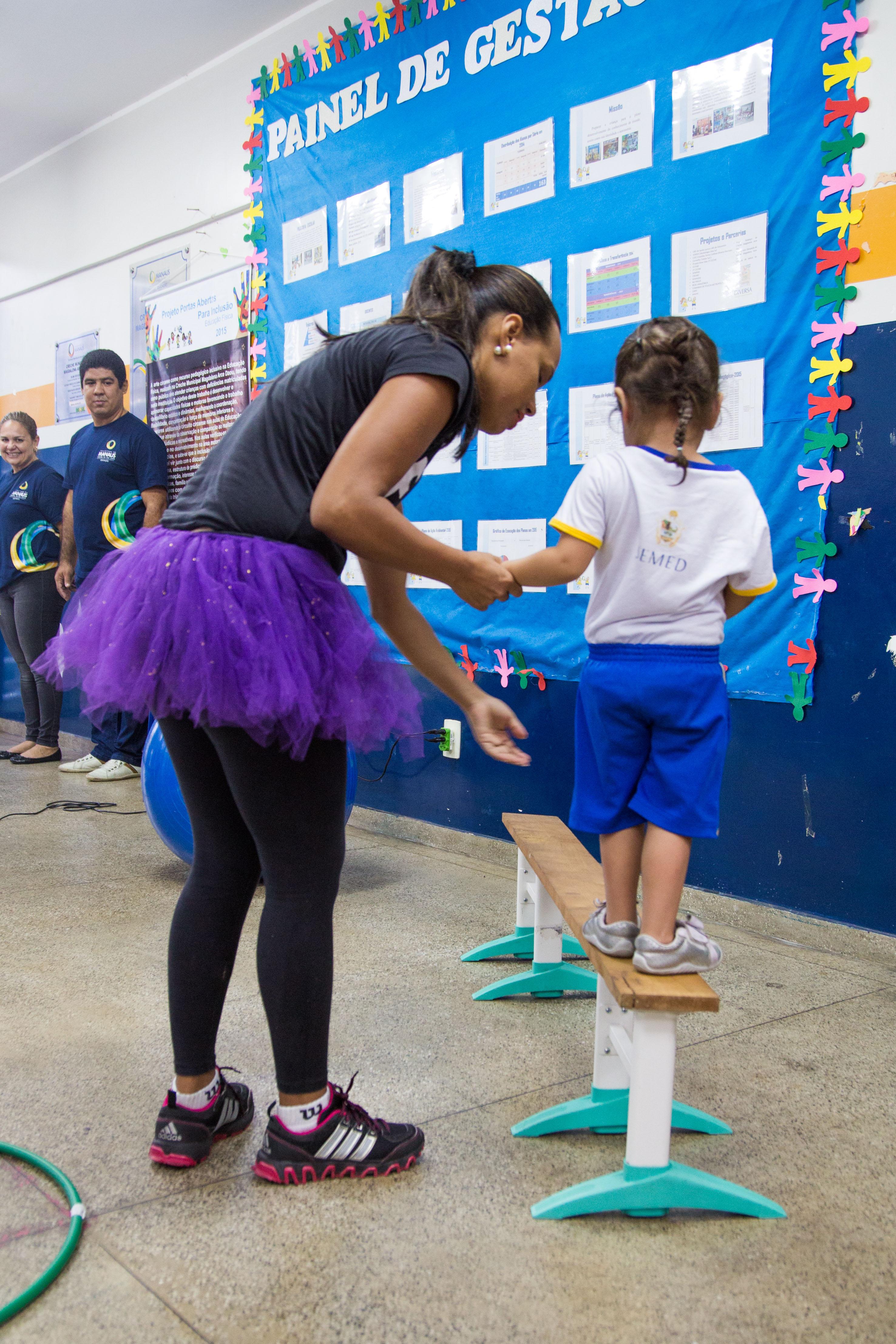 Uma garota de cerca de 4 anos se equilibra sobre uma tábua de madeira. Uma educadora a segura pelas mãos e a guia.