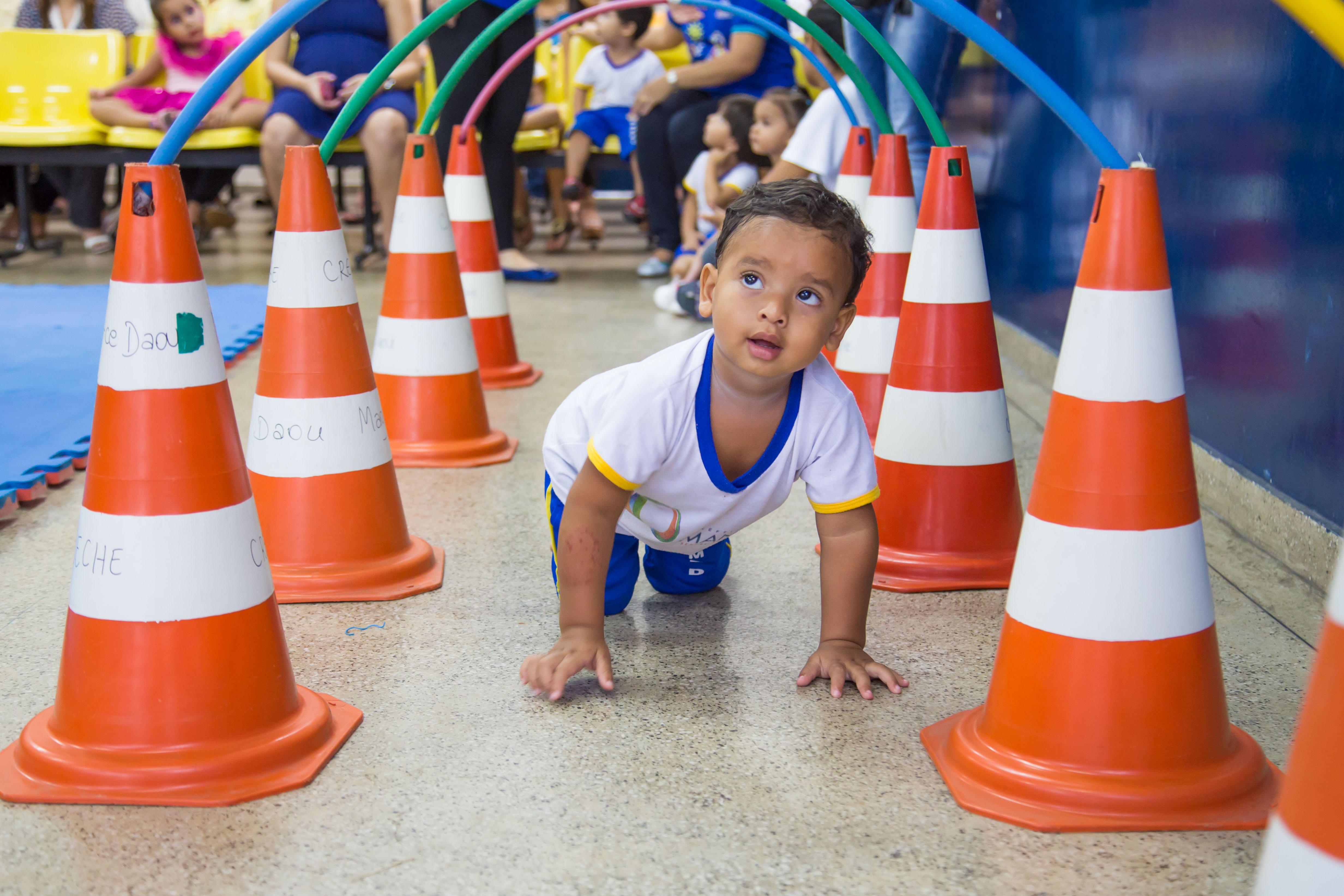 Um garoto pequeno engatinha por baixo de um túnel formado por bambolês e cones.