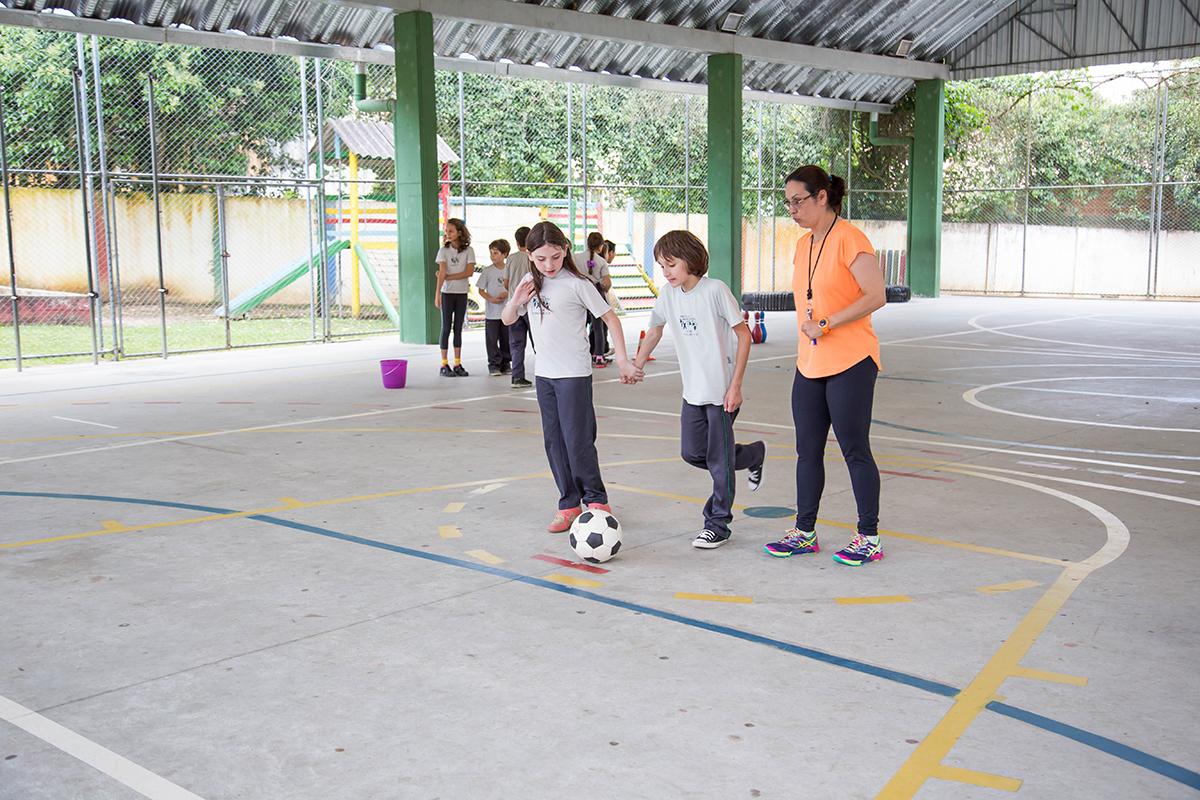 Pedro chuta uma bola contra o gol com auxílio de uma colega, que o segura pelas mãos. A professora está ao lado orientando o movimento.