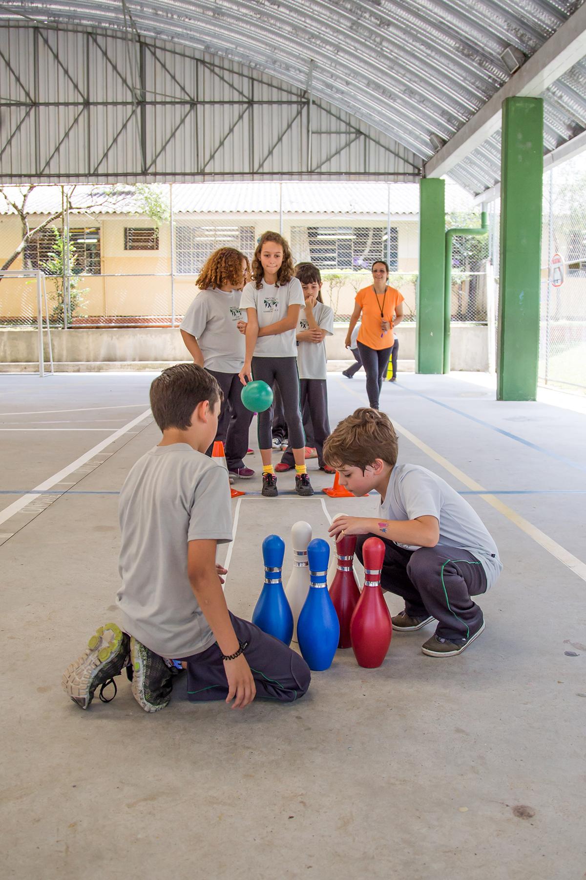 Dois garotos ajoelhados ao chão arrumam os pinos de boliche na posição correta. Atrás, uma fila de estudantes aguarda sua vez para derrubar os objetos. A primeira estudante da fila segura uma bola verde.