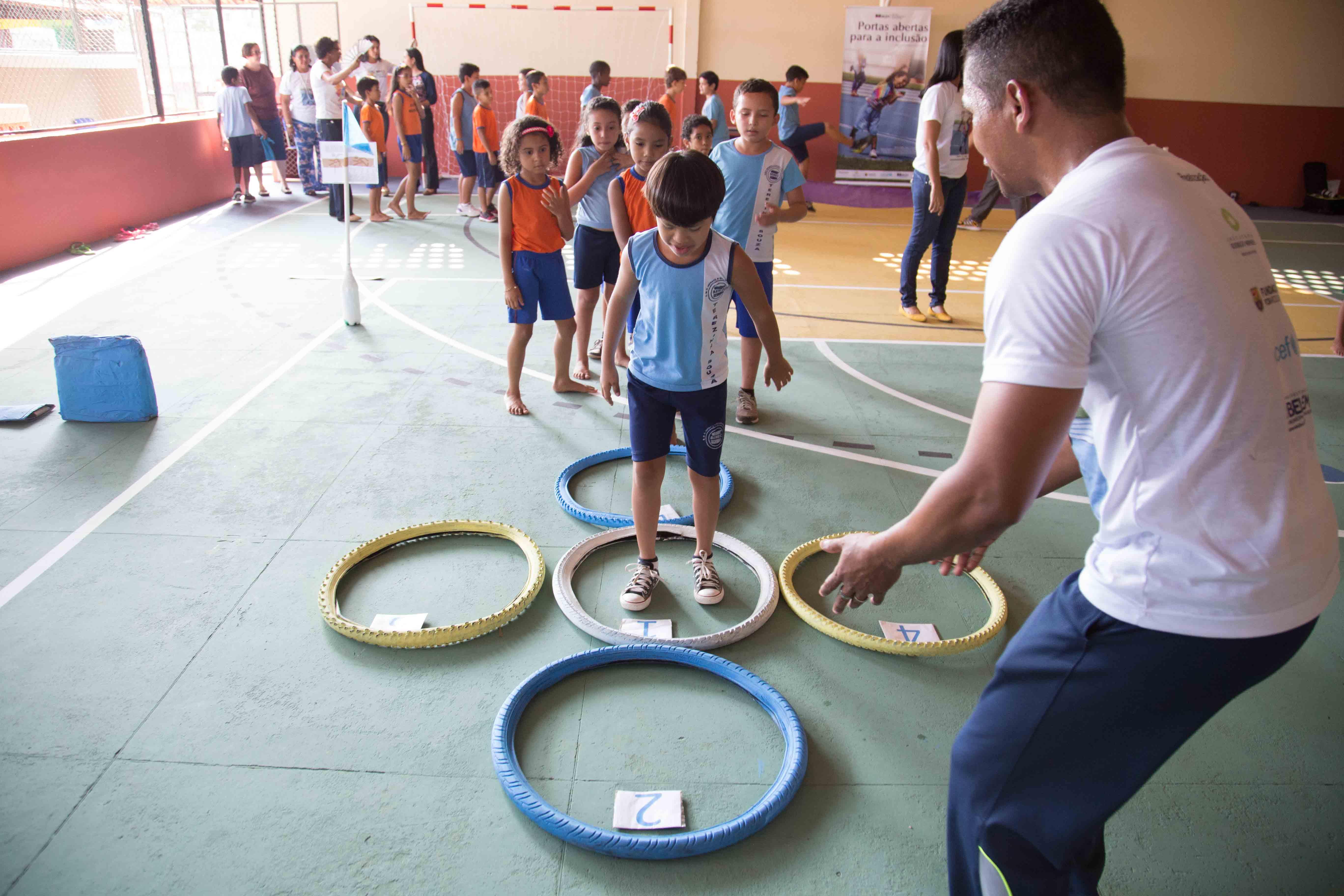 Quadra de esportes com os materiais que são usados durante o circuito de miniatletismo.