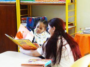 Professora mostra o livro a aluna com deficiência em uma cadeira de rodas..