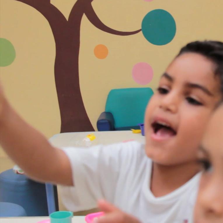 Bruno entrega um brinquedo para sua professora na sala de aula.