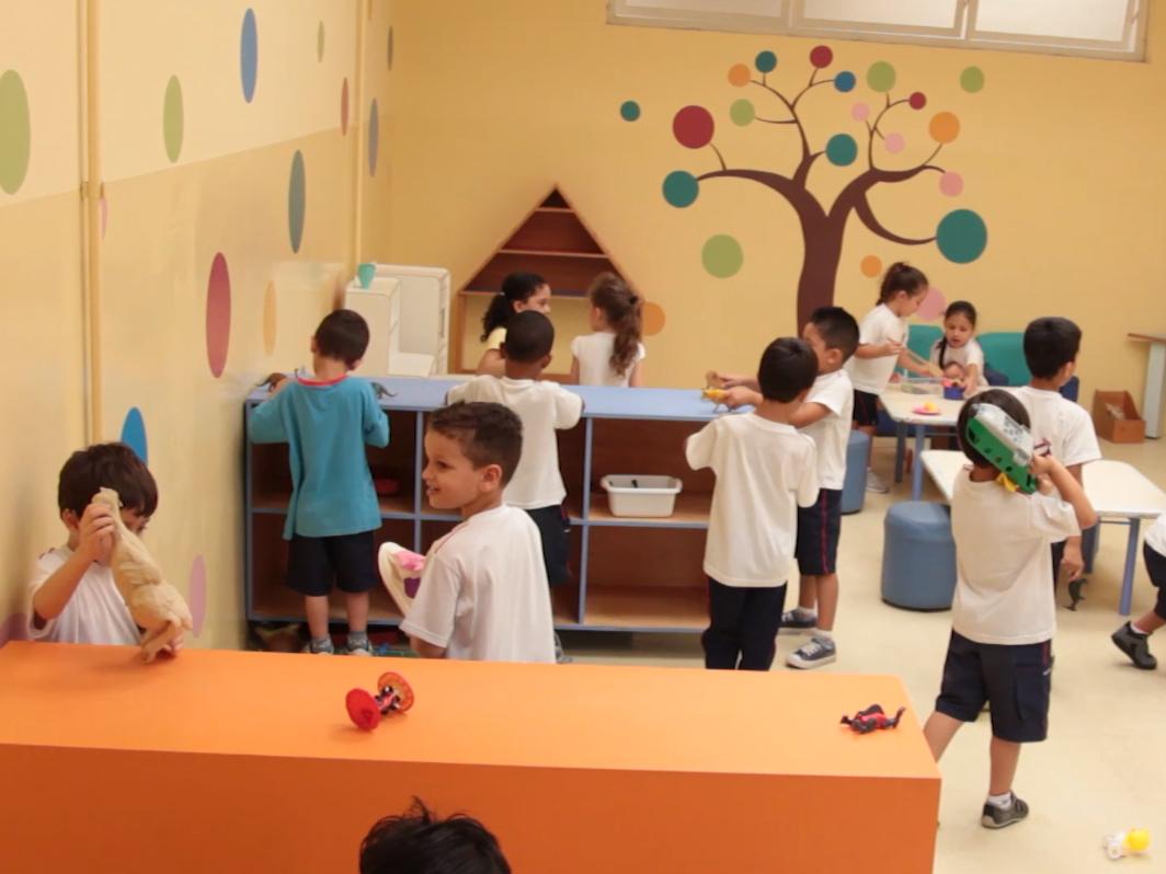 Um grupo de cerca de 10 crianças brinca com diversos objetos dentro de uma sala de aula.