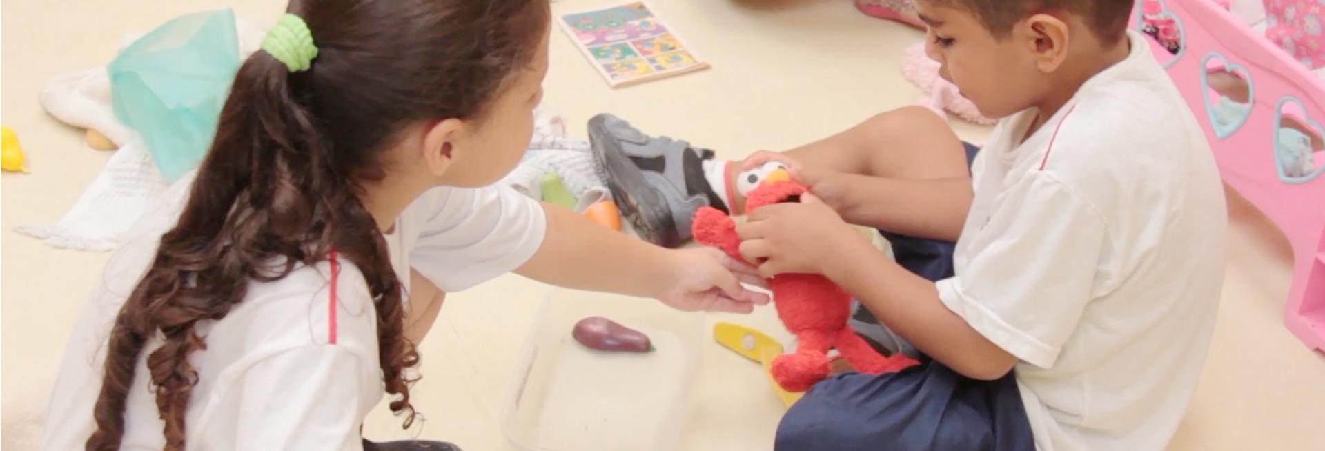 Bruno está sentado no chão em frente a uma colega. Eles brincam juntos com um boneco vermelho.