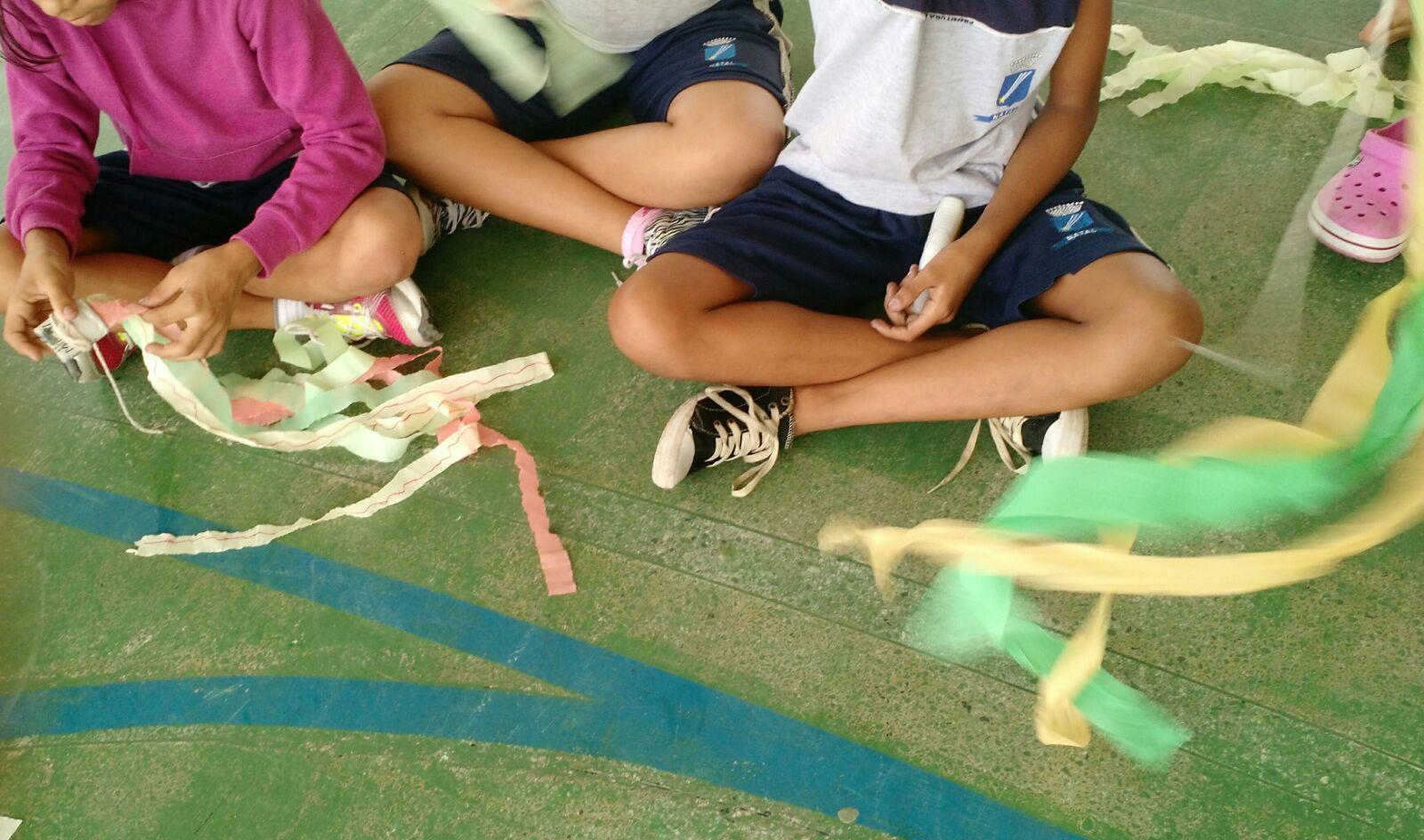 Três estudantes estão sentados no chão de uma quadra. Eles brincam com grandes fitas de papel crepom.