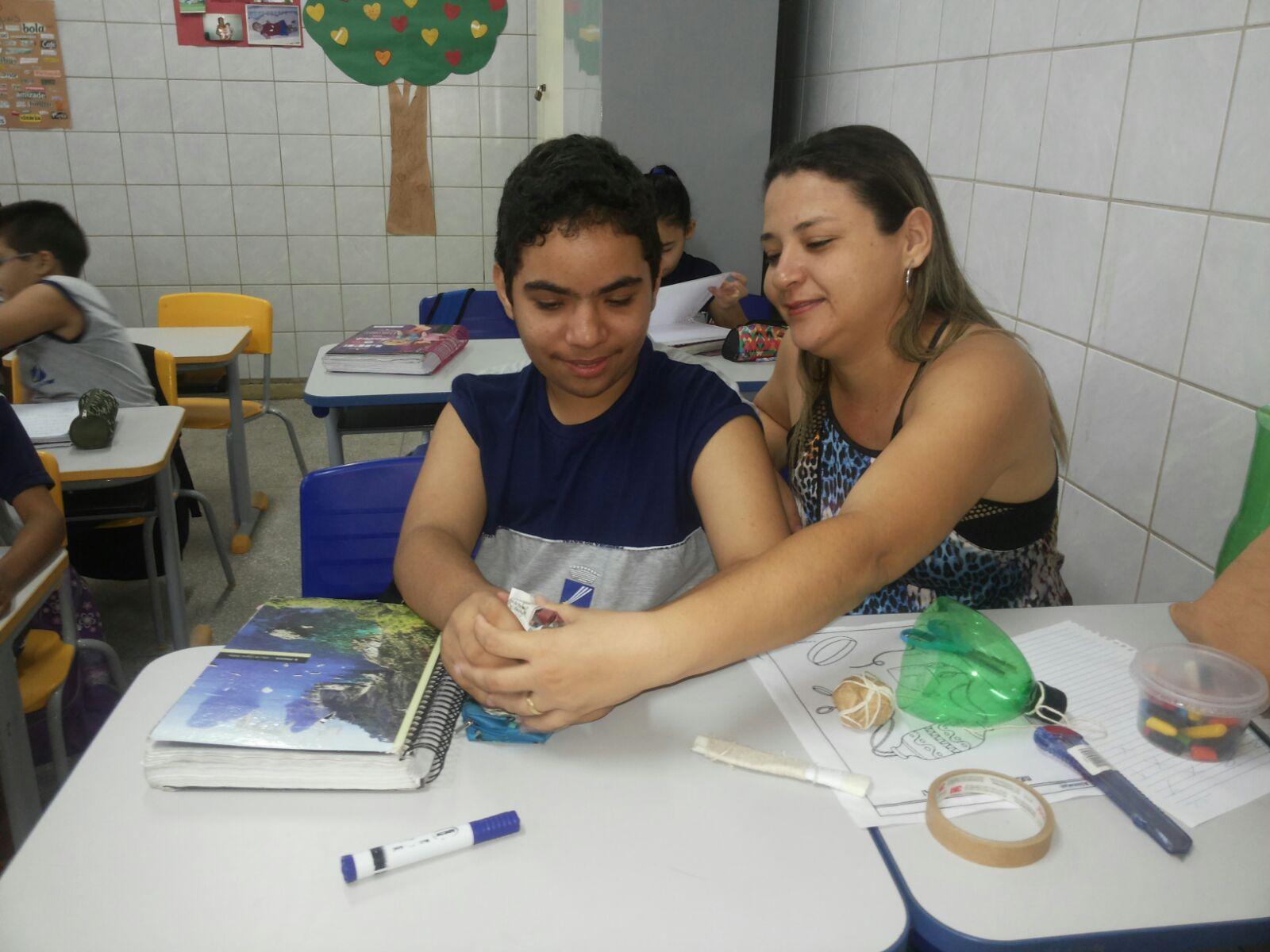 Professora auxilia estudante durante oficina de confecção de brinquedos. Os dois estão sentados lado a lado e sobre as carteiras há materiais como durex, garrafa, caneta, tesoura etc.