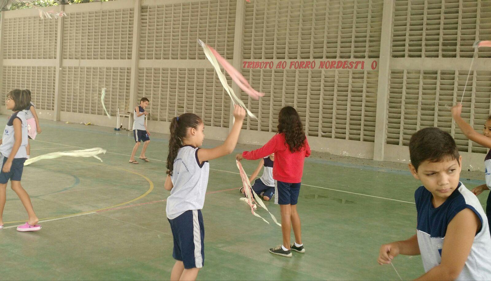 Crianças brincam com varetas com fitas de papel na ponta em quadra de esporte.