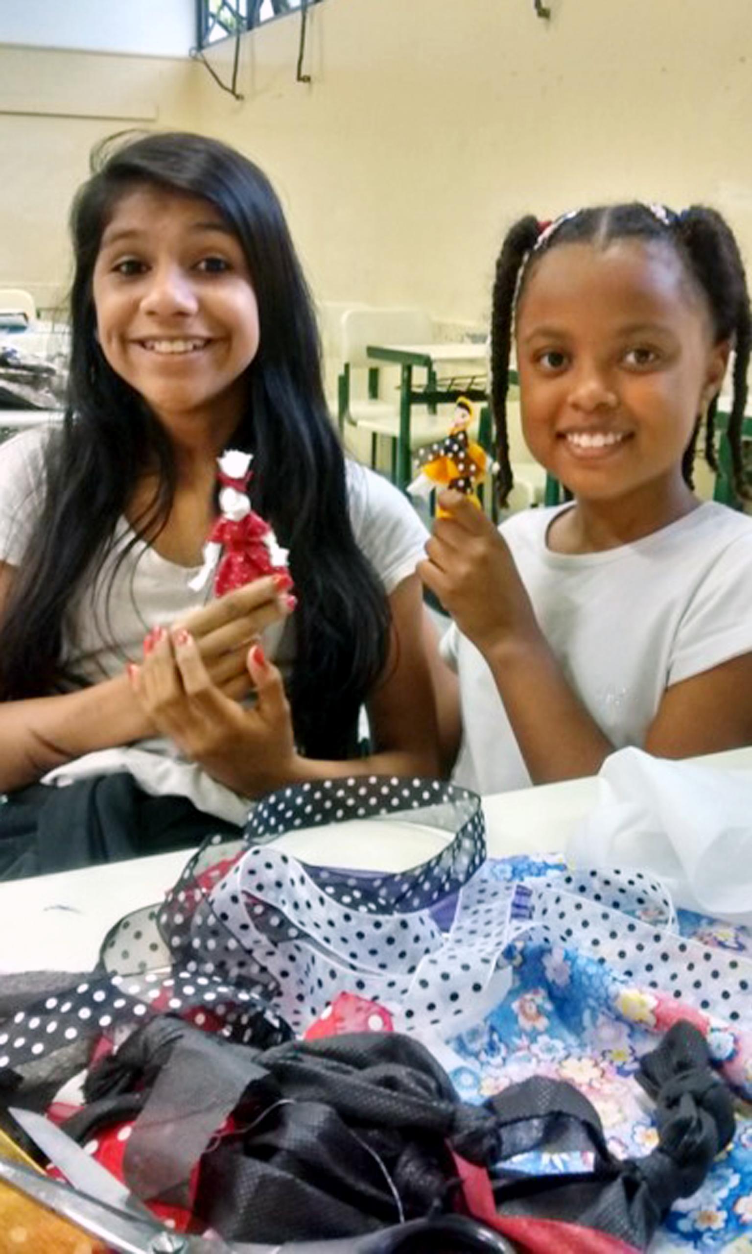 Duas alunas seguram as bonecas que confeccionaram. Elas estão diante de uma mesa repleta de retalhos de tecidos.