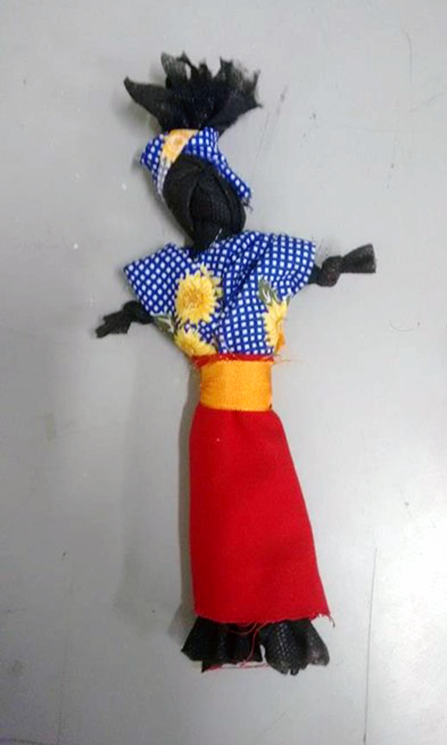 Boneca de pano preta com uma saia vermelha e uma blusa azul.