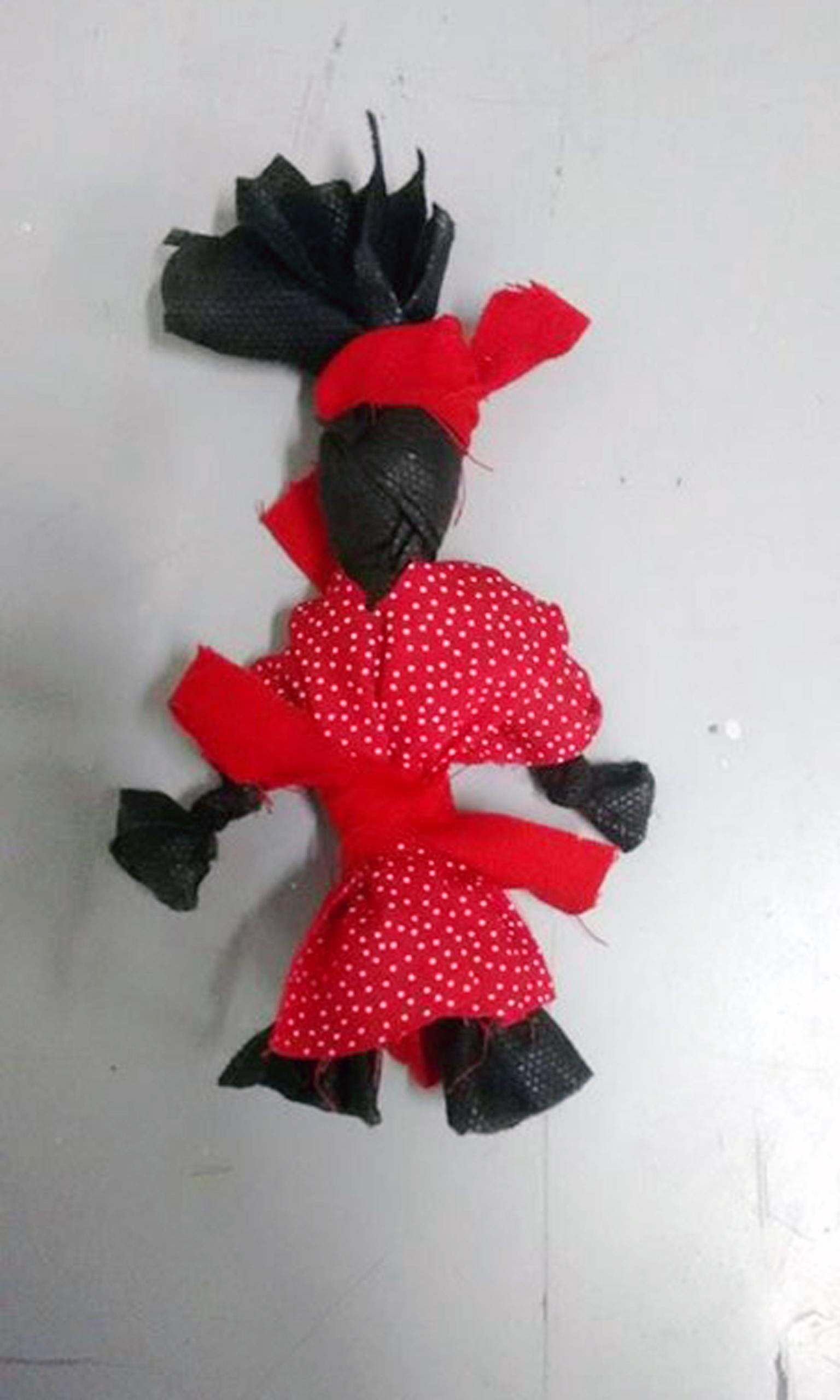 Boneca de pano preta com um vestido e um turbante vermelho.