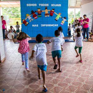 Cinco crianças correm segurando bexigas em pátio escolar. Atrás dela, um mural diz Somos todos iguais nas diferenças.