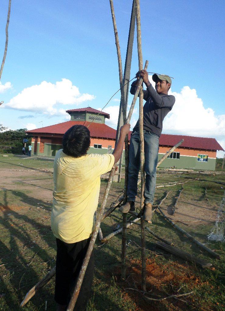 Um jovem está de pé em cima de uma estrutura de madeira, amarrando um pedaço de cipó. Debaixo, um senhor de camisa amarela o ajuda.