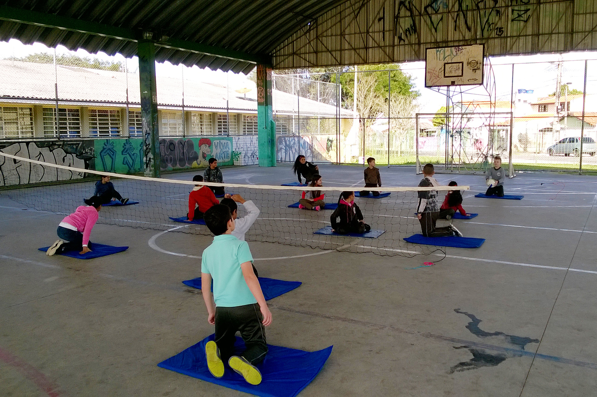 Um grupo de crianças joga vôlei sentado em uma quadra de esportes em uma escola. As crianças estão divididas em dois times, cada jogador está de joelhos sobre um colchonete no chão. A rede de vôlei no meio da quadra está no nível do chão.