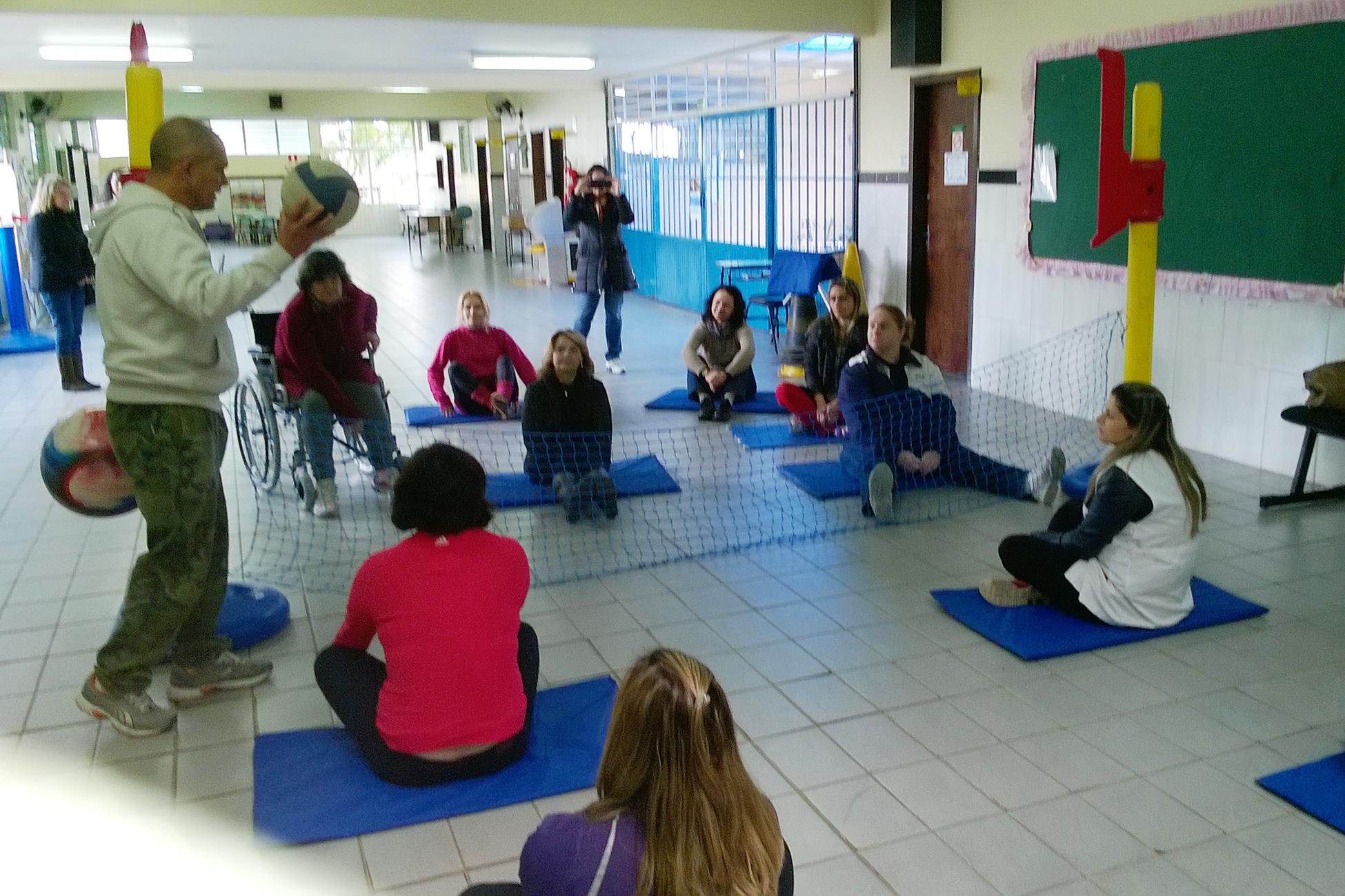 Grupo de professores joga vôlei sentado em pátio de escola.
