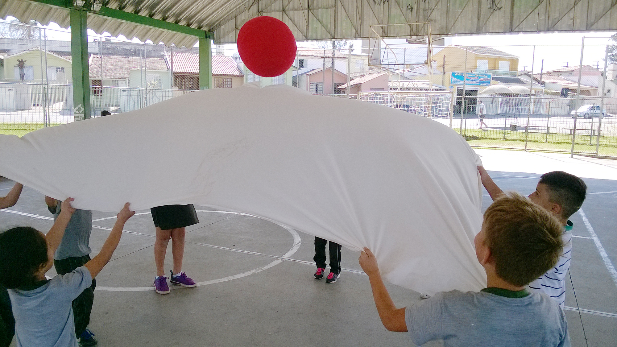 Em uma quadra, um grupo de crianças estica um grande lençol. Eles equilibram uma grande bola vermelha em cima do tecido.