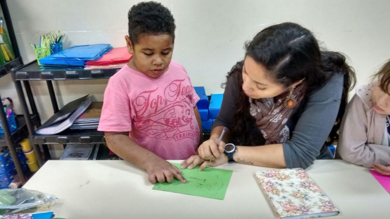 Micael e sua professora estão lado a lado, sentados diante de uma mesa, apontando e escrevendo em um papel verde.