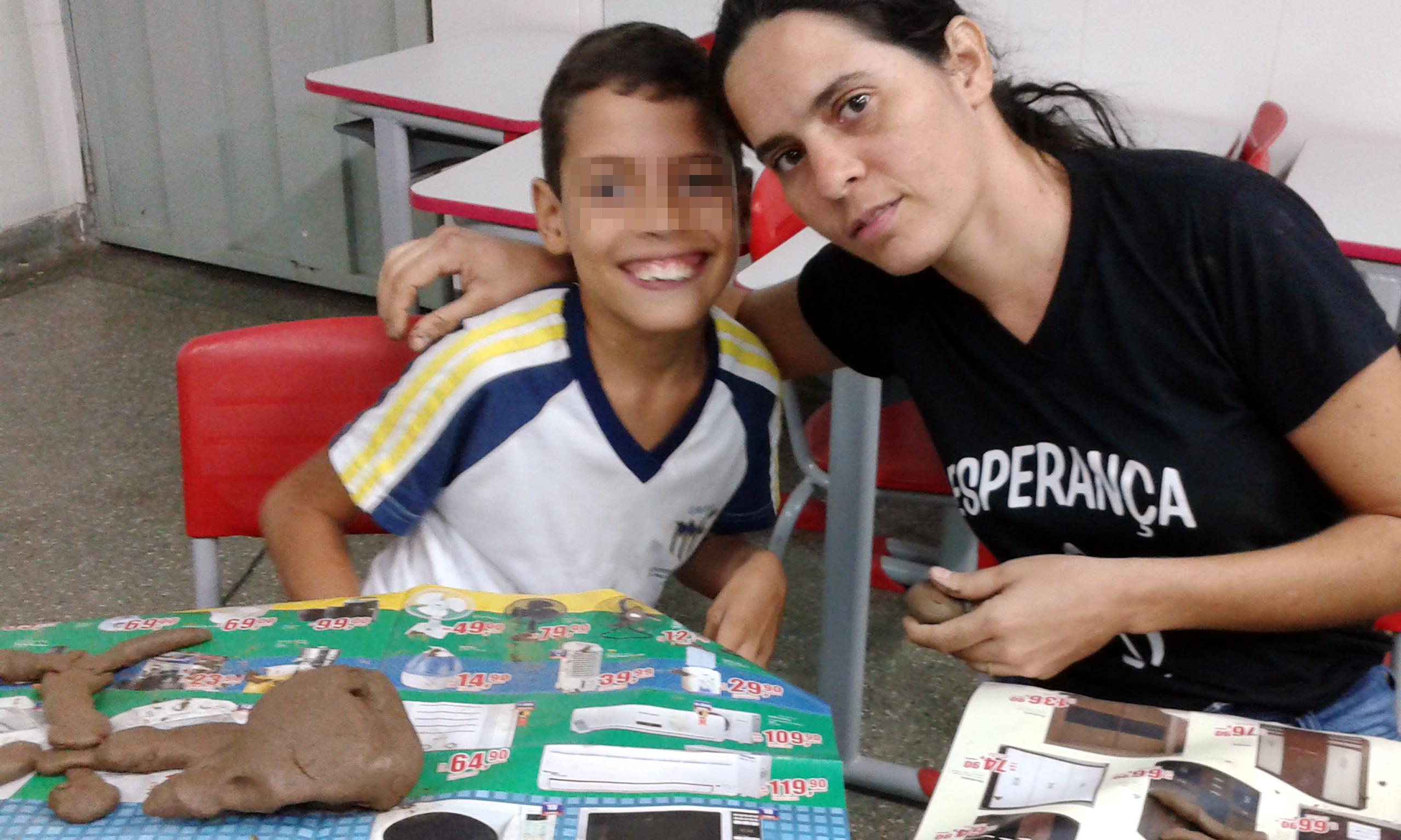 Um garoto e uma mulher sorriem para foto. Eles estão sentados diante de carteiras forradas com jornal e com pedaços de argila.