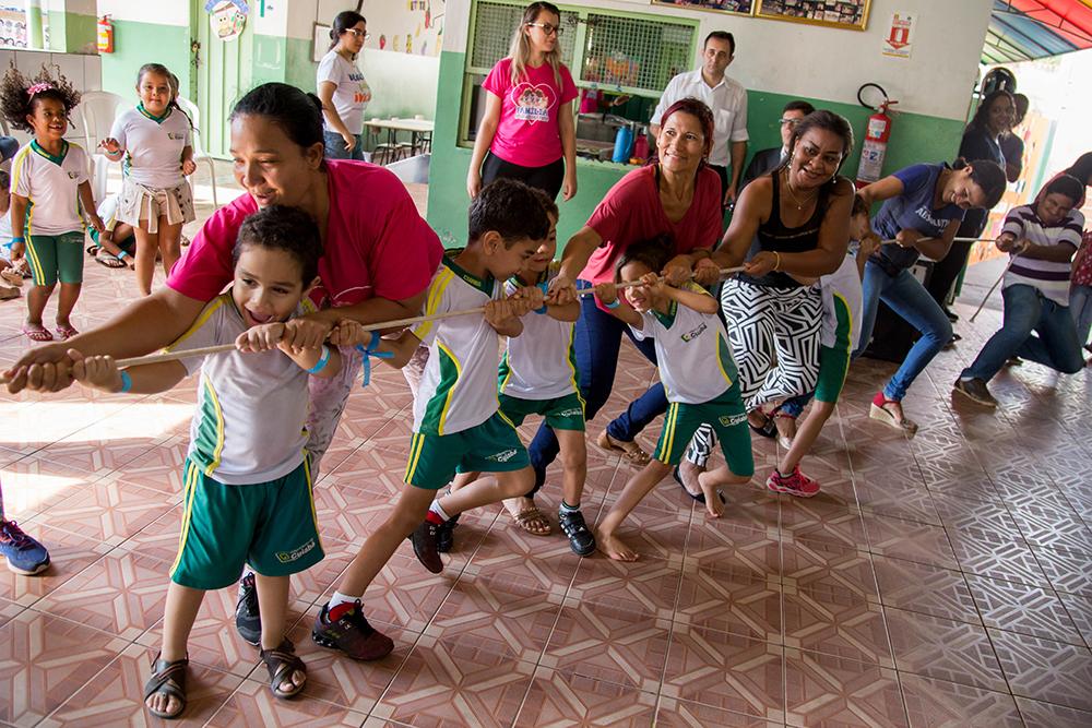 Time formado por três mulheres adultas e quatro crianças puxa uma corda durante brincadeira de cabo de guerra com as famílias.
