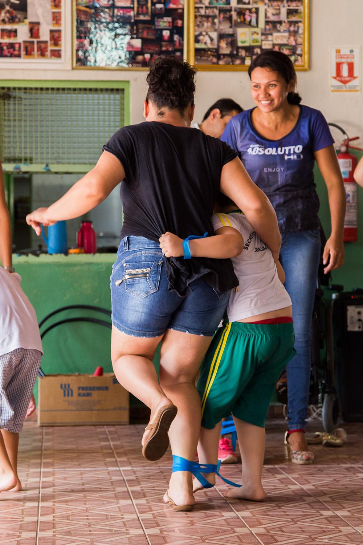Uma mulher e um garoto com as pernas amarradas um ao outro correm abraçados pelo pátio.