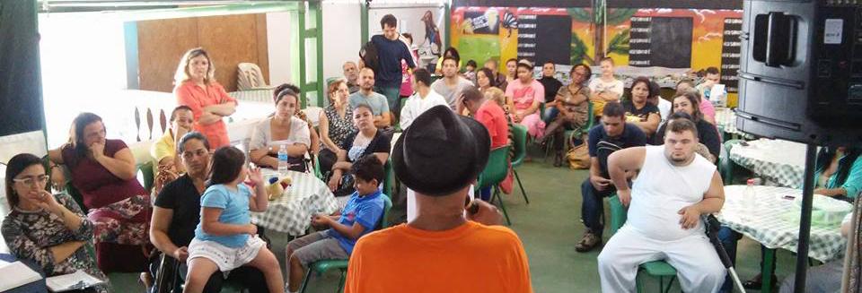Um grupo de cerca de 30 pessoas, entre adultos, adolescentes e crianças, estão sentados em um salão diante de um professor que segura um microfone.