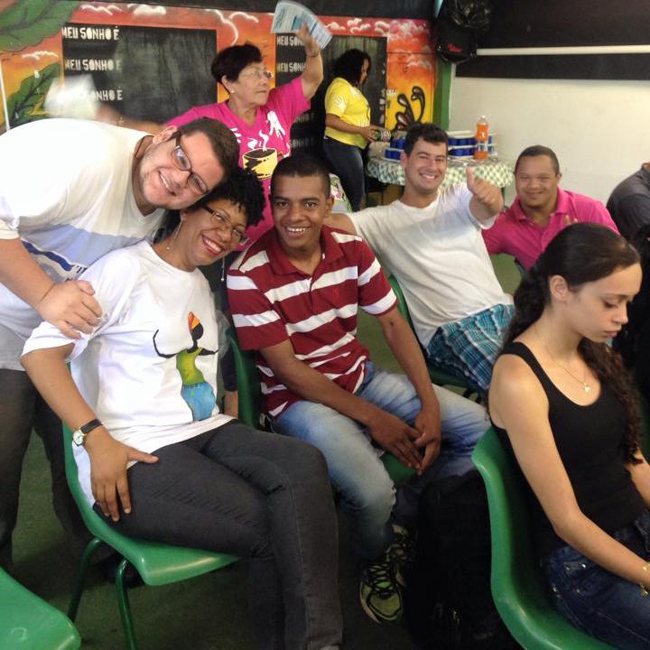 Grupo de familiares de estudantes sorri para a foto durante encontro.