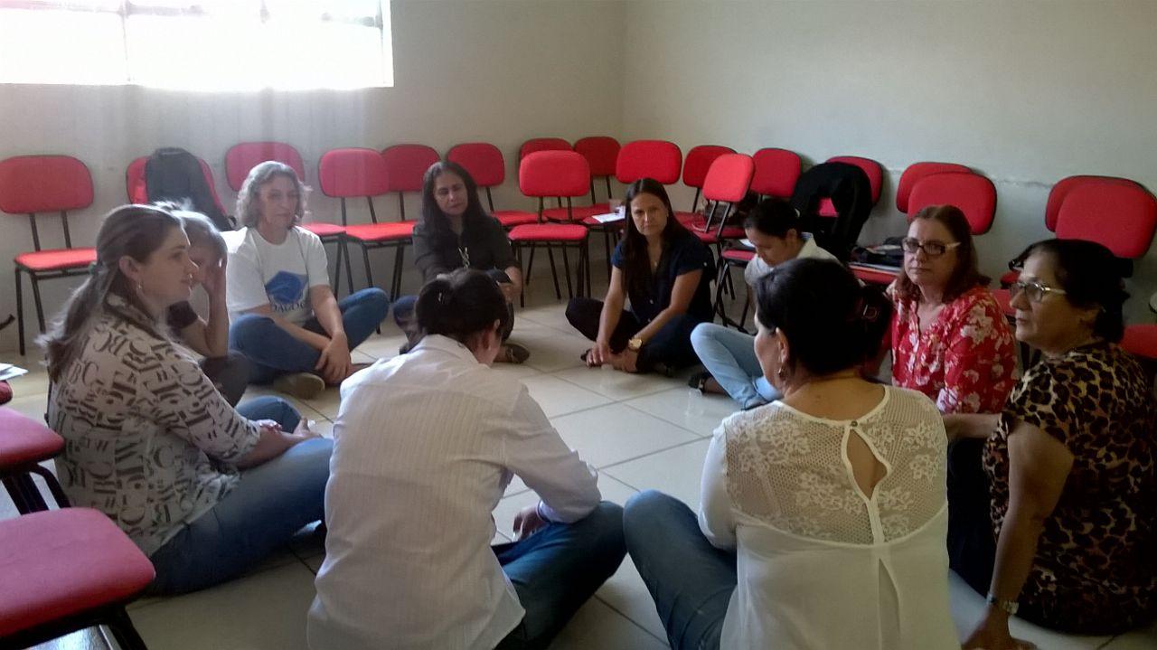 Grupo de professores está sentando no chão, em círculo, conversando.