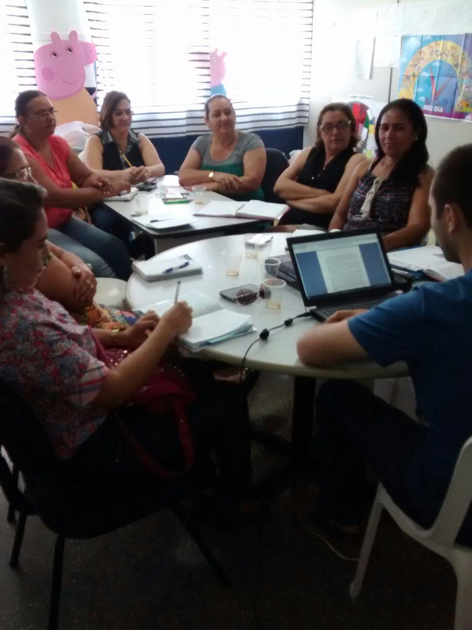 Um grupo de cerca de 10 educadores conversa ao redor de uma grande mesa.
