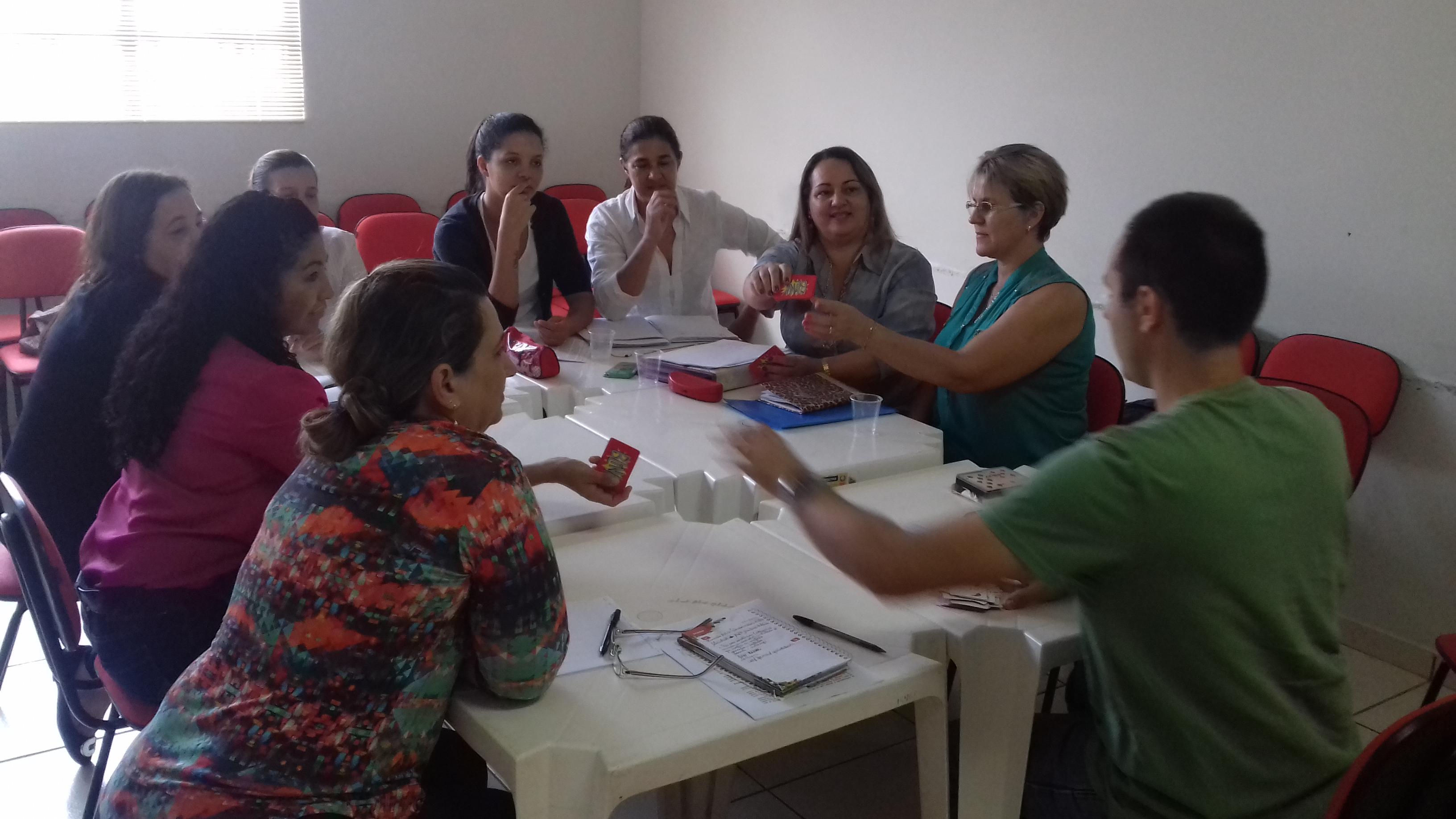 Um grupo de cerca de 10 educadores conversa ao redor de uma mesa.
