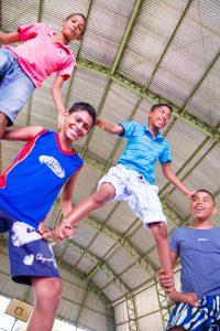 Quatro garotos adolescentes formam uma pirâmide humana.