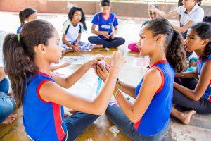Um grupo de estudantes está sentado em círculo em uma quadra escolar. No centro da roda, há muitos materiais como papéis, fitas, cola, tesoura. Eles manuseiam esses materiais para criar seus próprios brinquedos.