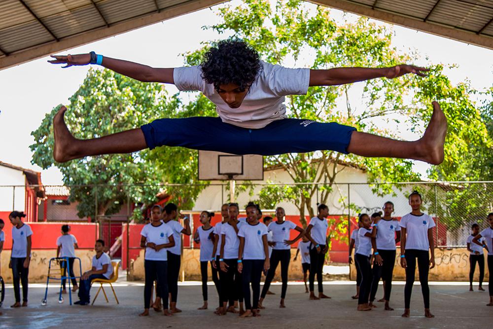 Garoto executa o salto frontal, esticando pernas e braços no ar.