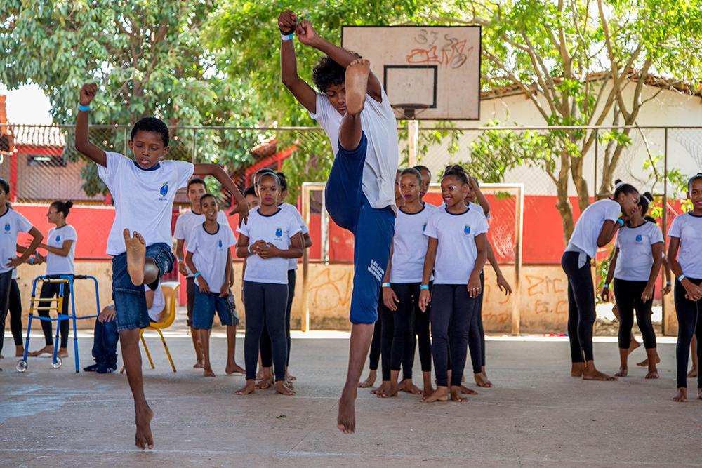 Dois meninos fazem movimento do salto tesoura, levantando alto uma das pernas.