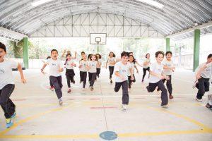 Crianças correm alinhadas em quadra de esportes escolar