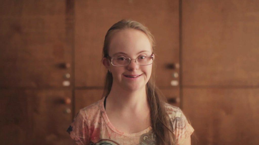 Renata, estudante do ensino médio com Síndrome de Down, aparece sorrindo para foto.