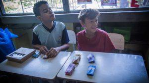 Dois garotos estão sentados em carteiras escolares. Eles manuseam o leitor de cédulas feito de caixa de papelão e as notas.
