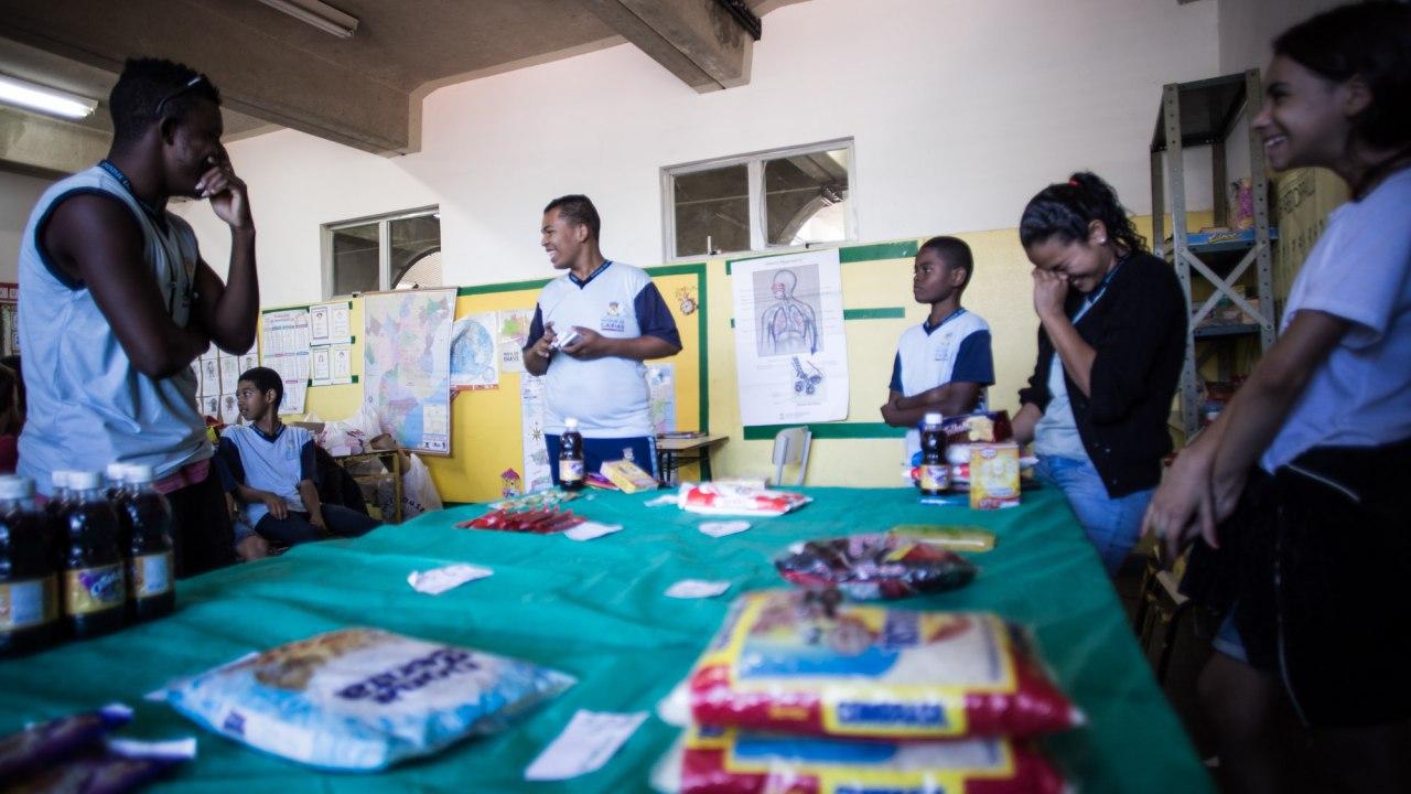 produtos de mercado como farinha, açúcar e macarrão estão sobre uma grande mesa dentro de uma sala de aula. Os alunos está em pé ao redor.